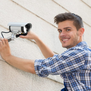 Young Happy Male Technician Fixing Cctv Camera On Wall